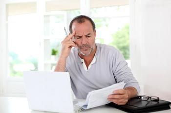 Is This Weird Habit Hurting Your Retirement Savings?: https://g.foolcdn.com/editorial/images/585833/man-looking-at-paper-document-concentrating-confused.jpg