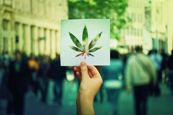 Where Will HEXO Be in 5 Years?: https://g.foolcdn.com/editorial/images/532051/hand-holding-up-paper-sheet-with-marijuana-leaf-with-crowded-street.jpg